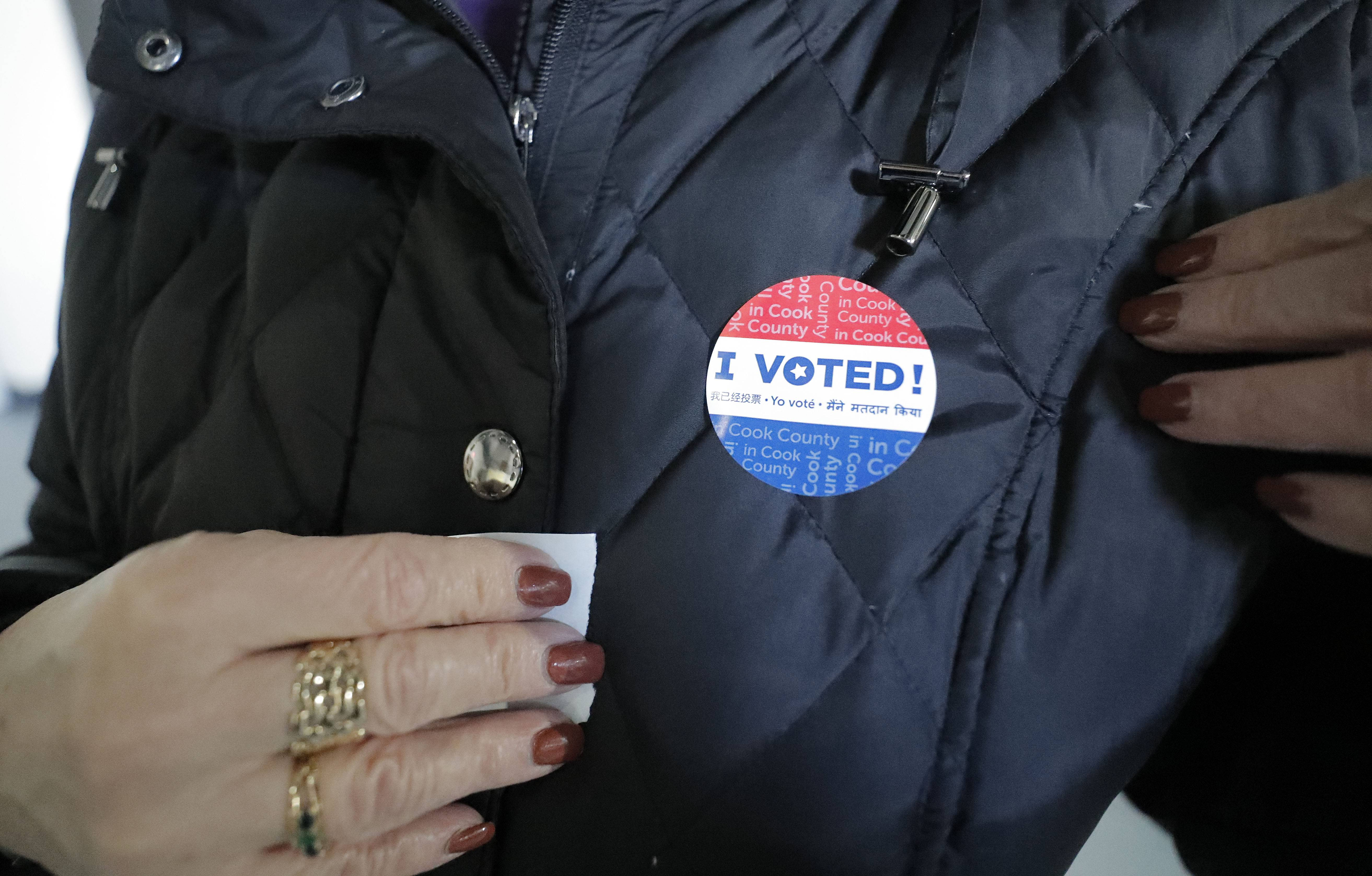 "Pat Biester of Schaumburg gets her ""I Voted"" sticker as early voting began Monday in suburban Cook County, including at the Trickster Art Gallery in Schaumburg."