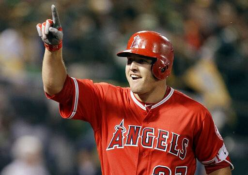 FIEL - In this April 3, 2017, file photo, Los Angeles Angels' Mike Trout celebrates after hitting a two-run home run off Oakland Athletics' Kendall Graveman in the third inning of a baseball game in Oakland, Calif. A person familiar with the negotiations tells The Associated Press Tuesday, March 19, 2019, that Trout and the Angels are close to finalizing a record $432 million, 12-year contract that would shatter the record for the largest deal in North American sports history. (AP Photo/Ben Margot, File)