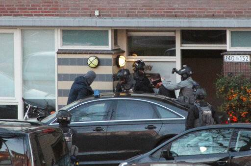 Dutch counter terrorism police prepare to enter a house after a shooting incident in Utrecht, Netherlands, Monday, March 18, 2019. A gunman killed three people and wounded nine others on a tram in the central Dutch city of Utrecht, sparking a manhunt that saw heavily armed officers with sniffer dogs zero in on an apartment building close to the shooting.