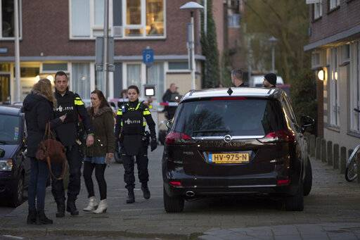 A tram passes in the background as flowers are seen in the foreground near the site of a shooting incident in a tram in Utrecht, Netherlands, Tuesday, March 19, 2019. A gunman killed three people and wounded others on a tram in the central Dutch city of Utrecht Monday March 18, 2019.