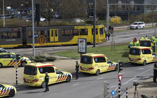 The body of one of three victims is covered with a white sheet as it lies next to a tram after a shooting incident in Utrecht, Netherlands, Monday, March 18, 2019. A gunman killed three people and wounded nine others on a tram in the central Dutch city of Utrecht, sparking a manhunt that saw heavily armed officers with sniffer dogs zero in on an apartment building close to the shooting.
