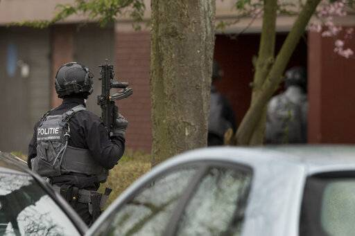 Dutch police stand guard outside a house where the suspect of a shooting incident in a tram was arrested in Utrecht, Netherlands, Monday, March 18, 2019. A gunman killed three people and wounded nine others on a tram in the central Dutch city of Utrecht.