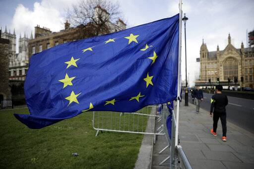 A European flag placed by anti-Brexit remain in the European Union supporters flies backdropped by the Houses of Parliament, at right, in London, Monday, March 18, 2019. British Prime Minister Theresa May was making a last-minute push Monday to win support for her European Union divorce deal, warning opponents that failure to approve it would mean a long - and possibly indefinite - delay to Brexit. Parliament has rejected the agreement twice, but May aims to try a third time this week if she can persuade enough lawmakers to change their minds.