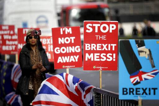 A tourist takes a selfie next to placards placed by anti-Brexit supporters stand opposite the Houses of Parliament in London, Monday, March 18, 2019. British Prime Minister Theresa May was making a last-minute push Monday to win support for her European Union divorce deal, warning opponents that failure to approve it would mean a long - and possibly indefinite - delay to Brexit. Parliament has rejected the agreement twice, but May aims to try a third time this week if she can persuade enough lawmakers to change their minds.