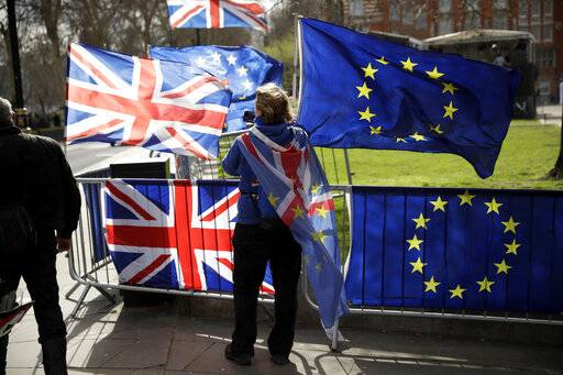 An anti-Brexit supporter stands by European and British Union flags placed opposite the Houses of Parliament in London, Monday, March 18, 2019. British Prime Minister Theresa May was making a last-minute push Monday to win support for her European Union divorce deal, warning opponents that failure to approve it would mean a long - and possibly indefinite - delay to Brexit. Parliament has rejected the agreement twice, but May aims to try a third time this week if she can persuade enough lawmakers to change their minds.