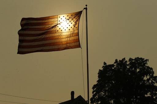 ADVANCE FOR USE TUESDAY, MARCH 19, 2019 AND THEREAFTER-FILE - In this Aug. 2, 2017 file photo, the evening sun shines through a U.S. flag flying in the wind in Tacoma, Wash., against a sky made hazy with smoke from wildfires, as the National Weather Service issued an excessive heat warning for western Washington and Oregon. An AP data analysis of records from 1999-2019 shows that in weather stations across America, hot records are being set twice as often as cold ones. (AP Photo/Ted S. Warren, File)
