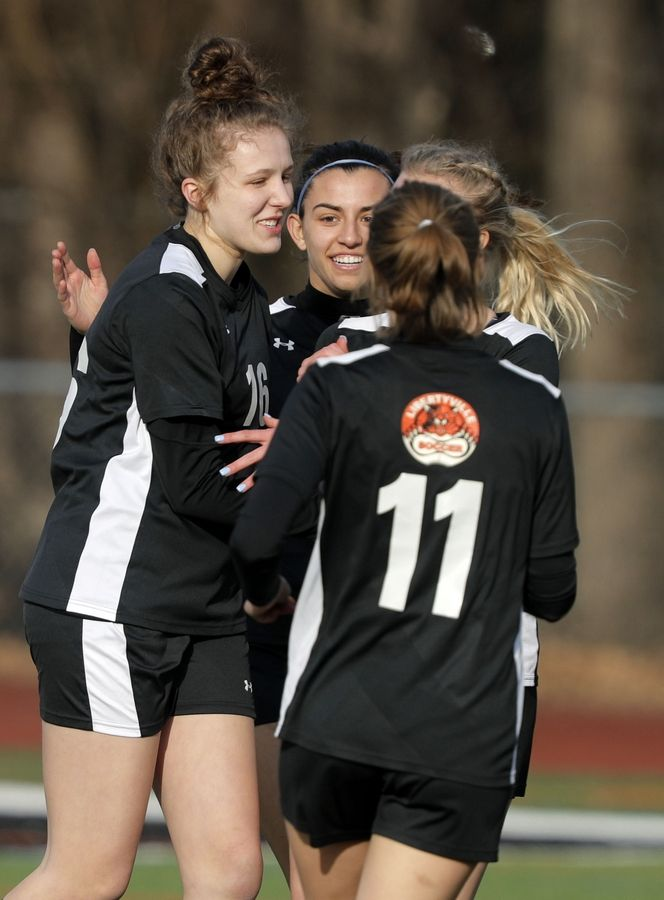 Teammates celebrate with Libertyville's Lauren Huber, left, after her goal during their game against New Trier Tuesday at Libertyville High School.
