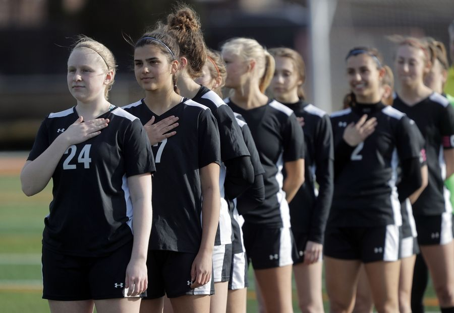 Libertyville's players stand for the national anthem during girls soccer action Tuesday at Libertyville High School.