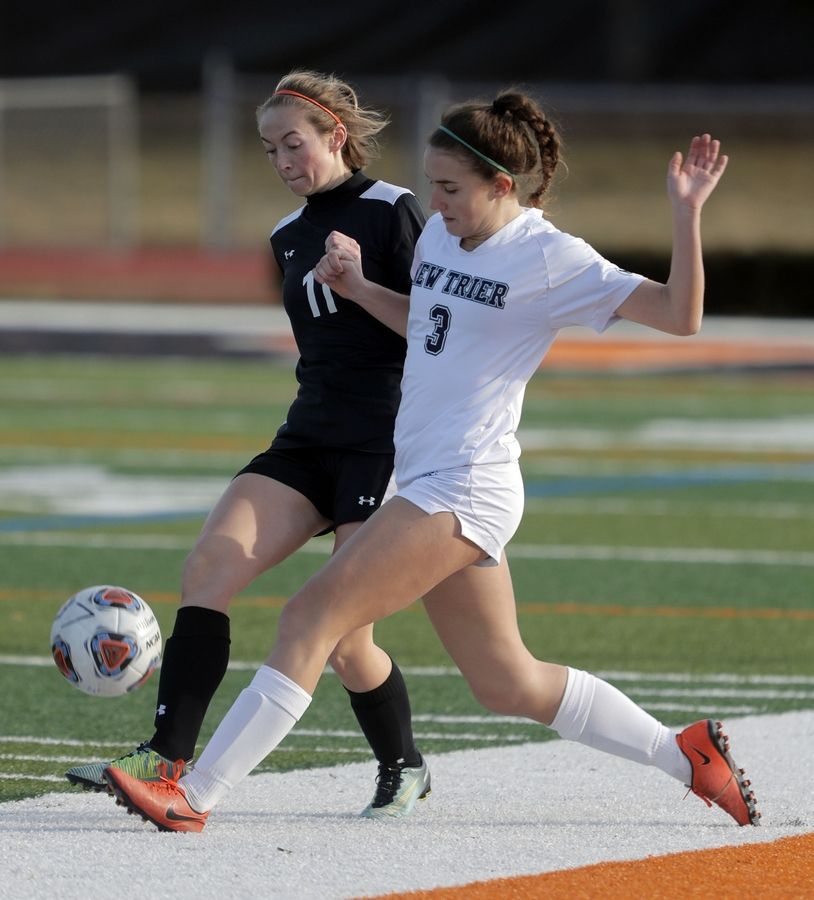 Libertyville's Faith Roberts, left, and New Trier's Juliette Lana battles for the ball during girls soccer action Tuesday at Libertyville High School.