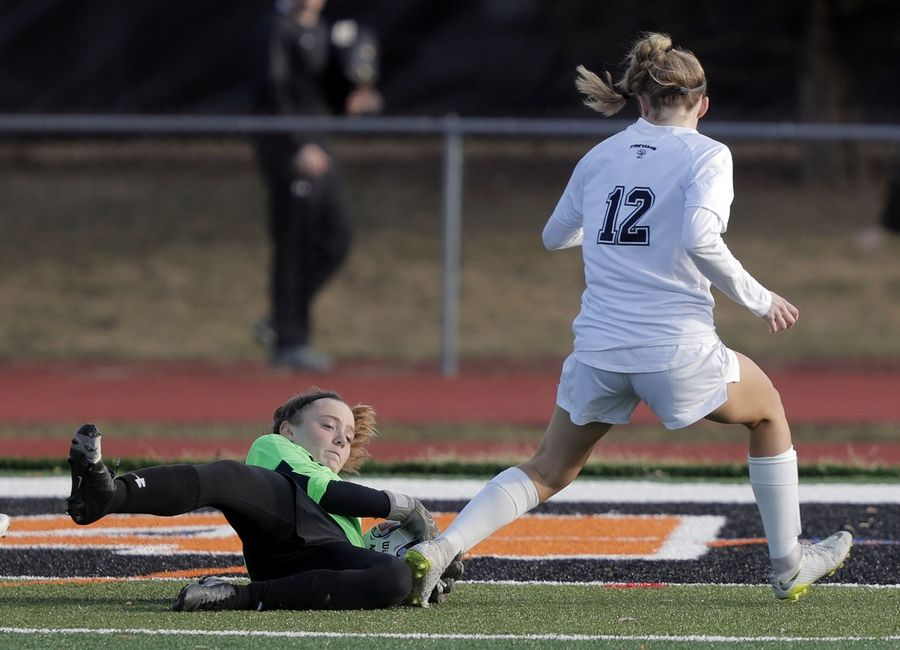 Libertyville goalie Abby Noonan, left, makes a save on New Trier's Maggie Gifford during girls soccer action Tuesday at Libertyville High School.