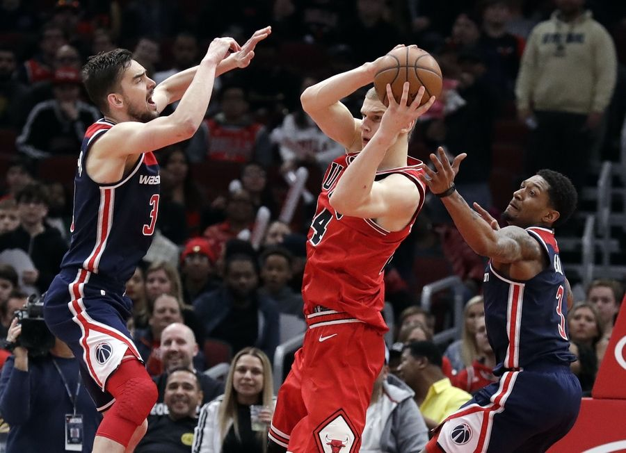 Chicago Bulls forward Lauri Markkanen, center, looks to pass the ball as Washington Wizards guard/forward Tomas Satoransky, left, and guard Bradley Beal defend during overtime of an NBA basketball game Wednesday, March 20, 2019, in Chicago. The Bulls won 126-120.