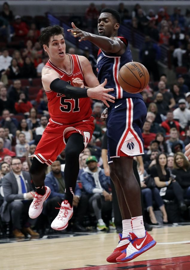 Chicago Bulls guard Ryan Arcidiacono, left, passes the ball as Washington Wizards forward Bobby Portis defends during overtime an NBA basketball game Wednesday, March 20, 2019, in Chicago. The Bulls won 126-120.