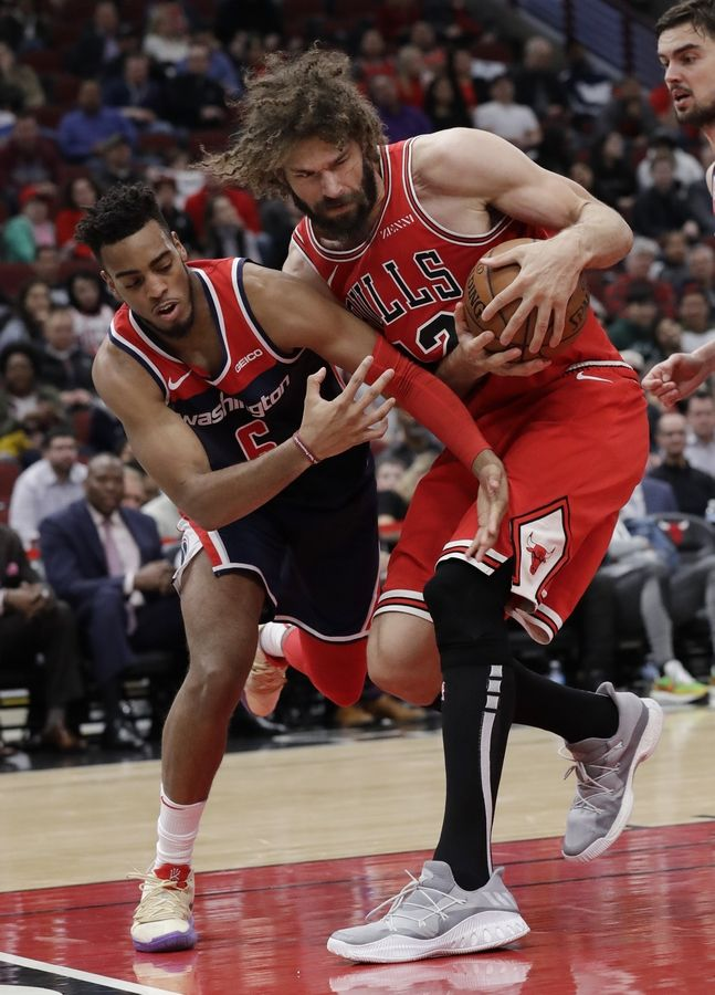 Chicago Bulls center Robin Lopez, right, pulls in a rebound next to Washington Wizards forward Troy Brown Jr., during the second half of an NBA basketball game Wednesday, March 20, 2019, in Chicago. The Bulls won 126-120 in overtime.