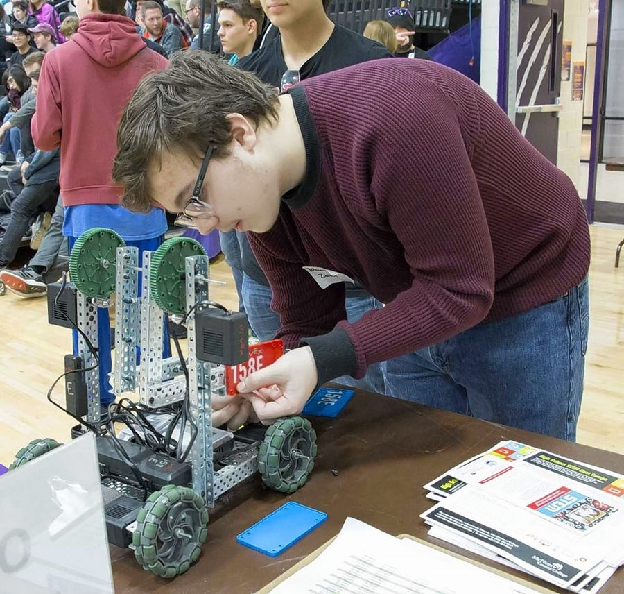 Huntley High School sophomore Nathaniel Zawarus installs a color competitor's tag on Huntley Team 5's robot before taking it to an advanced round during the recent McHenry County College 2019 Robotics Scrimmage High School event. Team 5 tied for first place with Huntley Team 8.