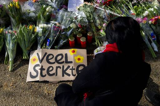 "A sign reads ""Lots of Strength"" as a mourner lays flowers at a makeshift memorial for victims of a shooting incident in a tram in Utrecht, Netherlands, Tuesday, March 19, 2019. A gunman killed three people and wounded others on a tram in the central Dutch city of Utrecht Monday March 18, 2019. (AP Photo/Peter Dejong)"