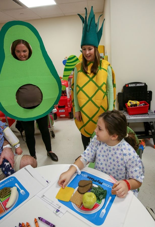 Dietitian Carrie Draney, left, and Laura Yudys, clinical nutrition manager, are part of the Produce Posse visiting children staying at Northwestern Medicine Central DuPage Hospital in Winfield. Nicollette Grande, 8, of Downers Grove picked up some lessons about healthy eating.