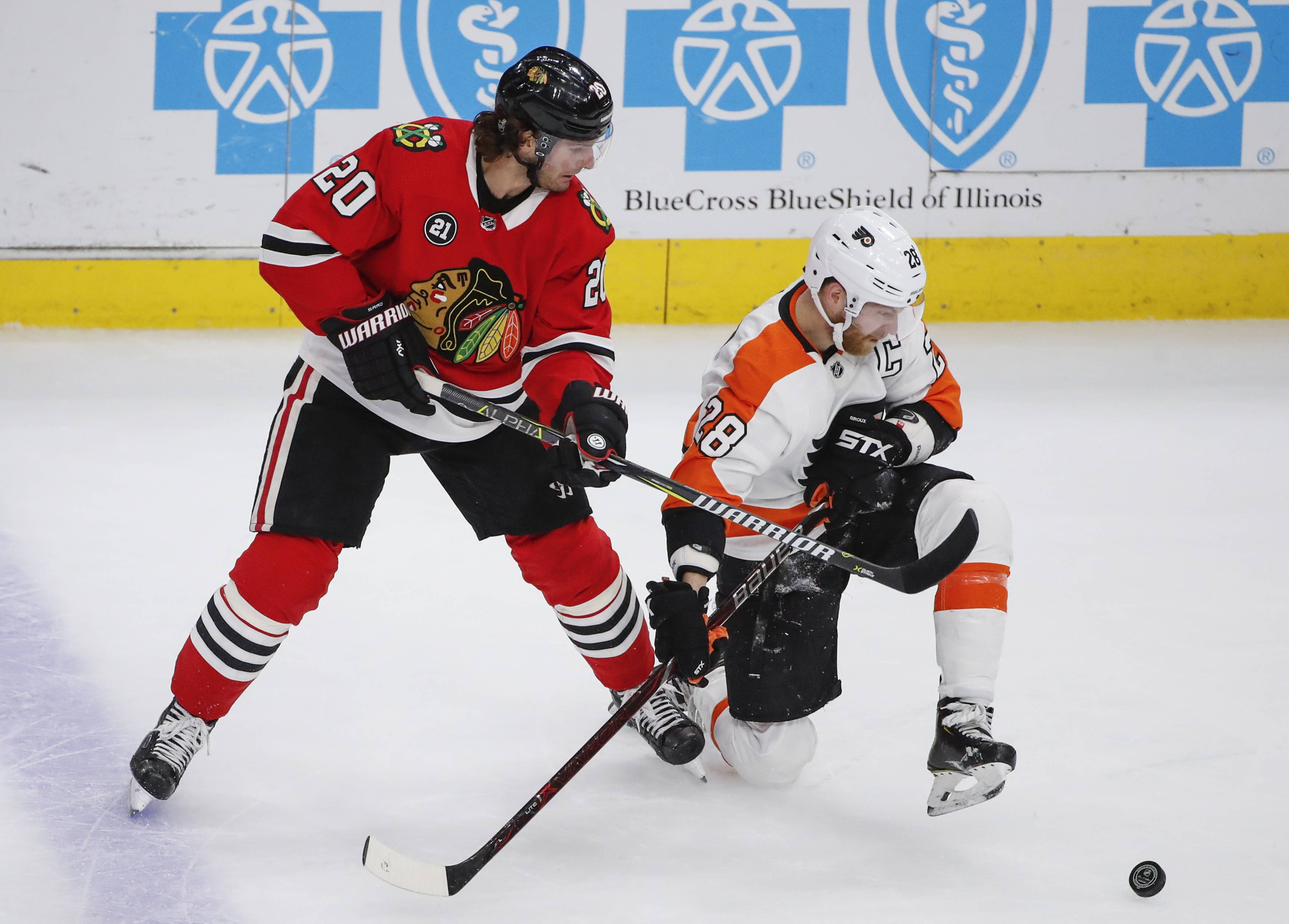 Chicago Blackhawks left wing Brandon Saad (20) battles for the puck with Philadelphia Flyers center Claude Giroux (28) during the second period of an NHL hockey game Thursday, March 21, 2019, in Chicago.
