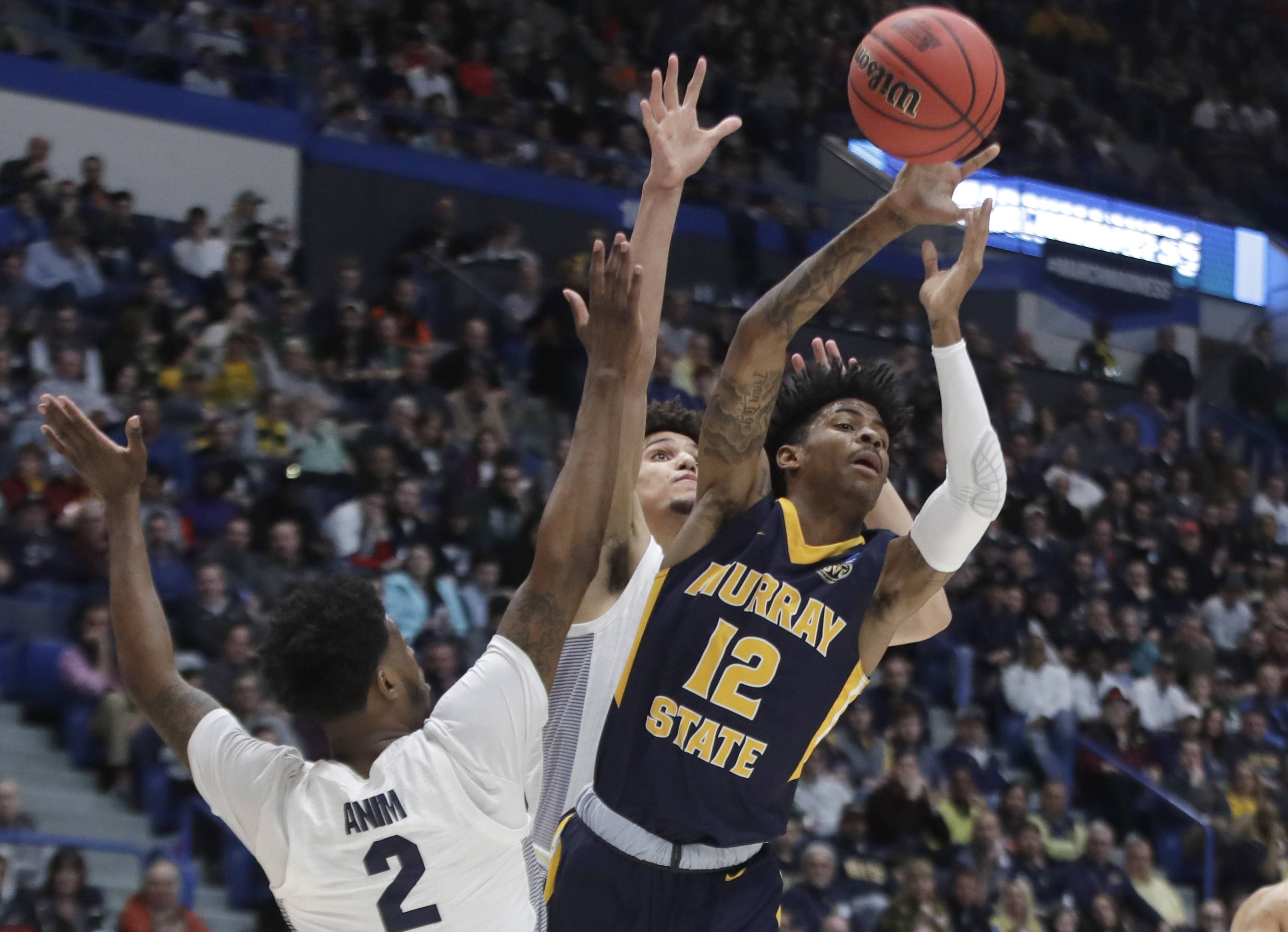 Murray State's Ja Morant (12) passes the ball under pressure from Marquette's Sacar Anim (2) and Brendan Bailey, behind, during the first half of a first round men's college basketball game in the NCAA Tournament, Thursday, March 21, 2019, in Hartford, Conn.
