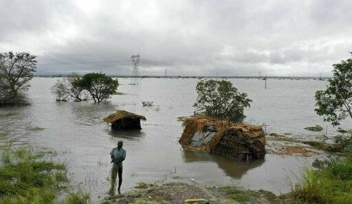 In this photo provided by ActionAid and taken on Sunday, March 17, 2019, locals look at a damaged bridge after Cyclone Idai hit, in Chimanimani, Zimbabwe. Mozambique began three days of national mourning on Wednesday, March 20 for more than 200 victims of Cyclone Idai, while the death toll in neighboring Zimbabwe rose to more than 100 from one of the most destructive storms to strike southern Africa in decades. (Tendai Chiwanza/ActionAid via AP)