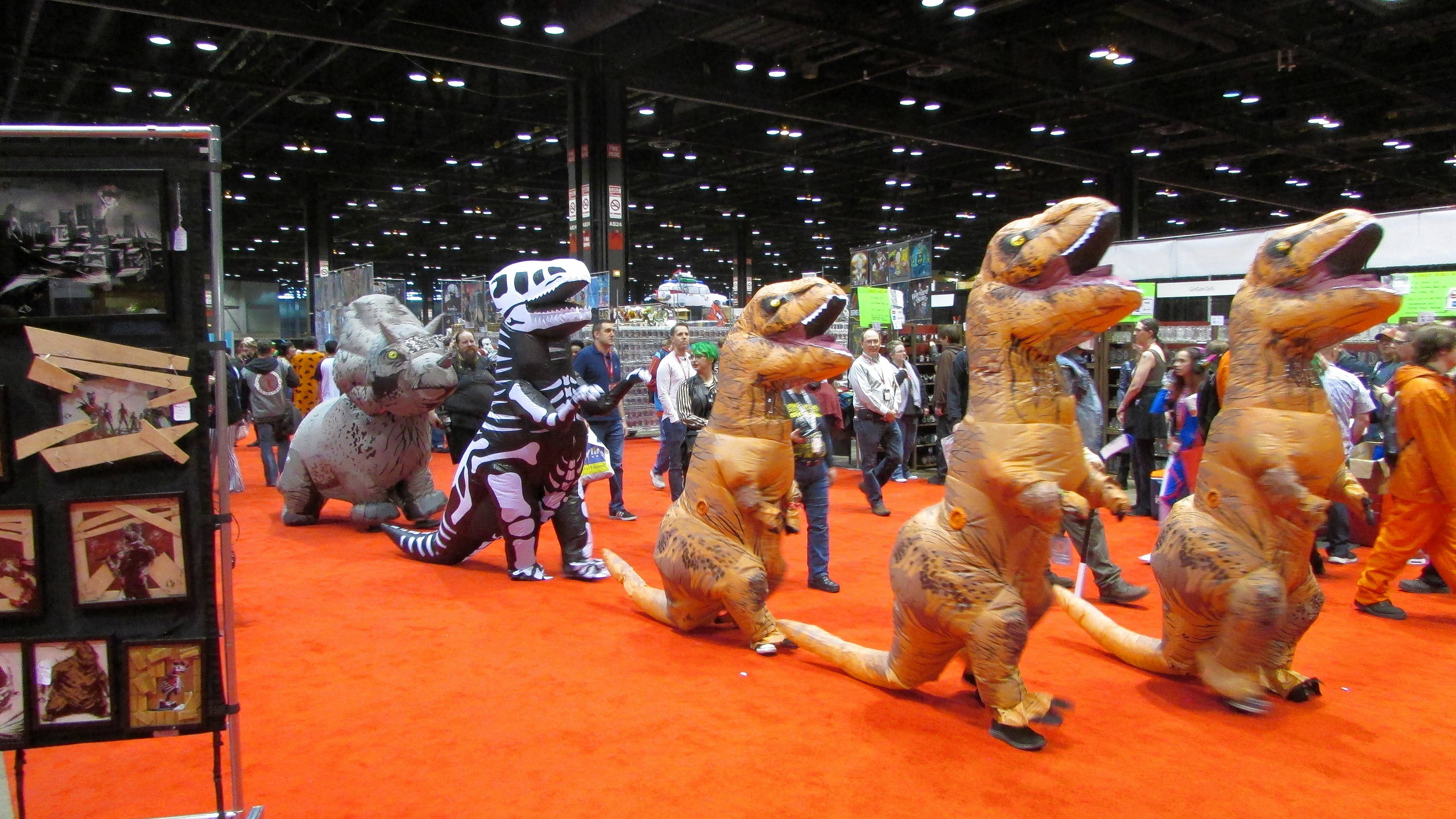 A parade of dinosaur costumes entertains the C2E2 show floor Friday.