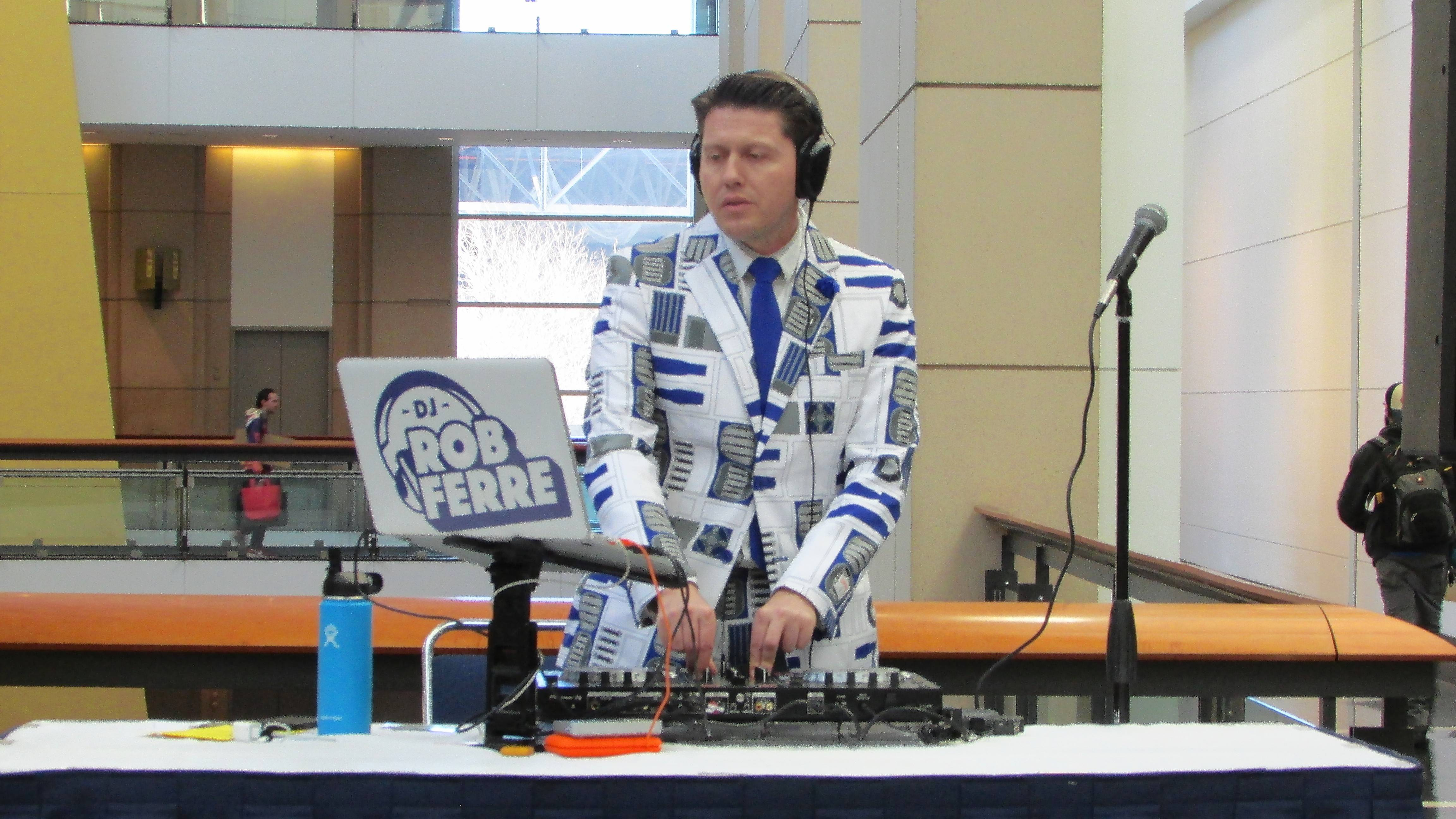 "DJ Rob Ferre plays a dance mix of John Williams' ""Jurassic Park"" theme Friday in the McCormick Place entrance hall."