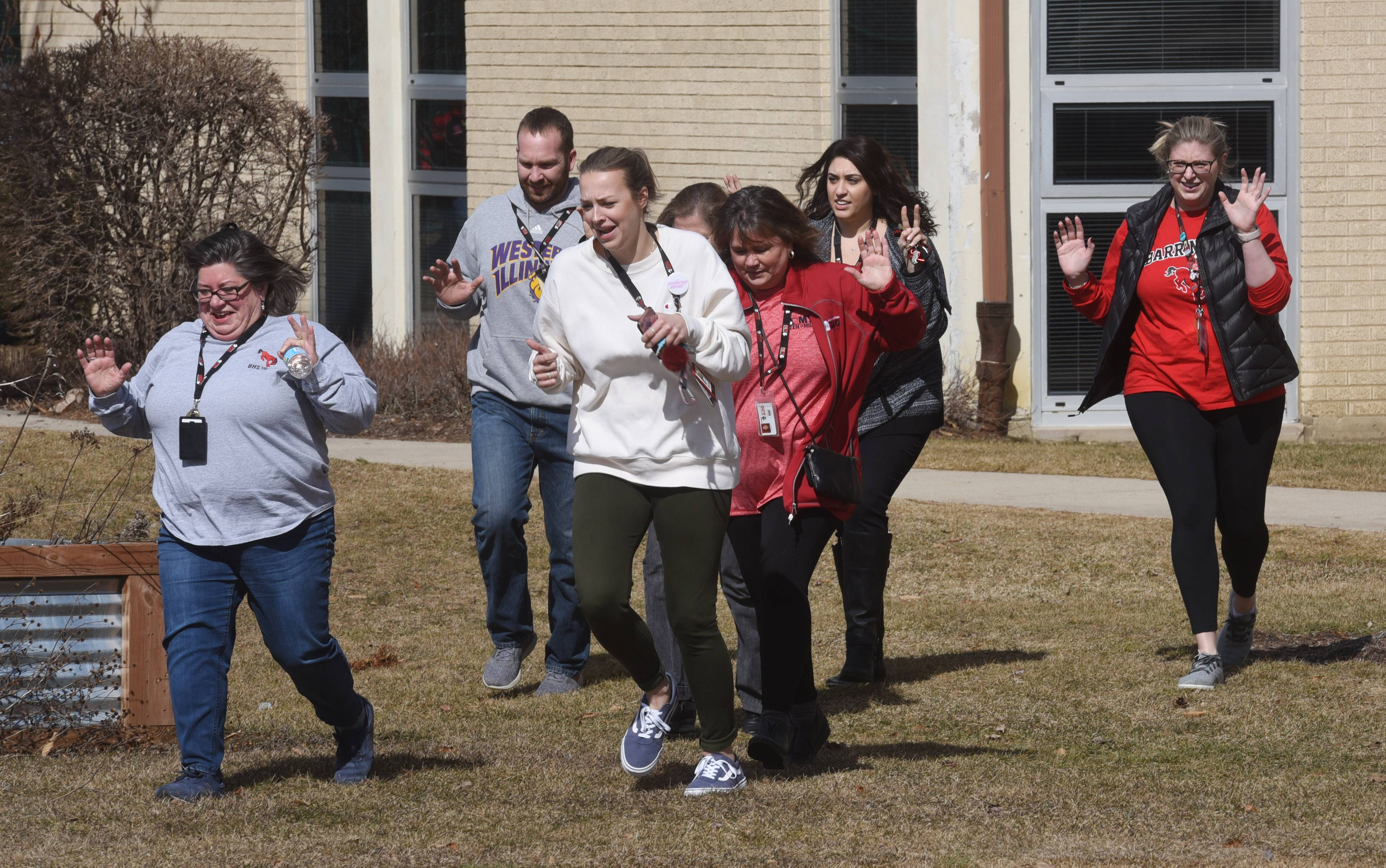 Barrington High School staff members run to safety during an active shooter drill Friday morning on campus.