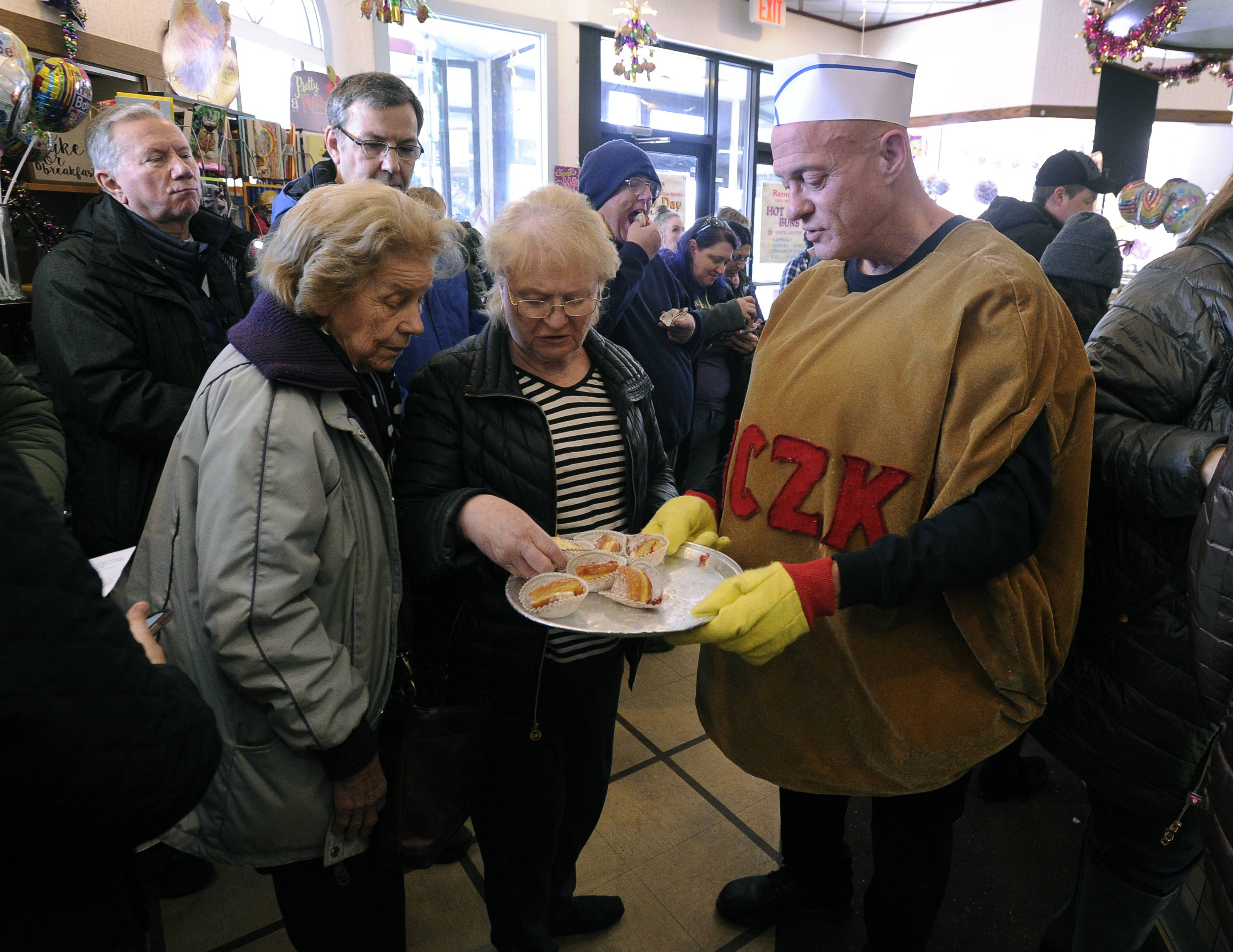 Robin Czerniak, brother of the owner of the Central Continental Bakery in Mount Prospect, hands out strawberry samples of the traditional polish pastry, paczki, to patrons waiting on orders to be picked up as the Fat Tuesday rush fills the bakery.
