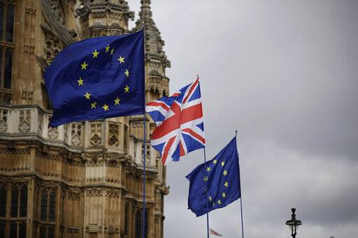 European flags and a British Union flag placed by anti-Brexit remain in the European Union supporters are blown by the wind across the street from the Houses of Parliament, not pictured, backdropped by Westminster Abbey in London, Monday, March 18, 2019. British Prime Minister Theresa May was making a last-minute push Monday to win support for her European Union divorce deal, warning opponents that failure to approve it would mean a long - and possibly indefinite - delay to Brexit. Parliament has rejected the agreement twice, but May aims to try a third time this week if she can persuade enough lawmakers to change their minds. (AP Photo/Matt Dunham)
