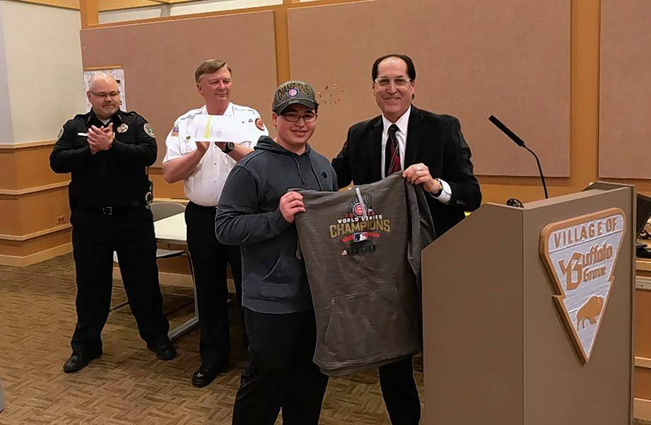 Buffalo Grove building inspector Joe Arizzi, right, hands a Cubs hoodie to 15-year-old Ari Melnick last week during a village ceremony honoring Arizzi's work to help the Stevenson High student through an asthma attack in February. Buffalo Grove Fire Chief Mike Baker, right, and Deputy Police Chief Scott Eisenmenger applaud in the background.