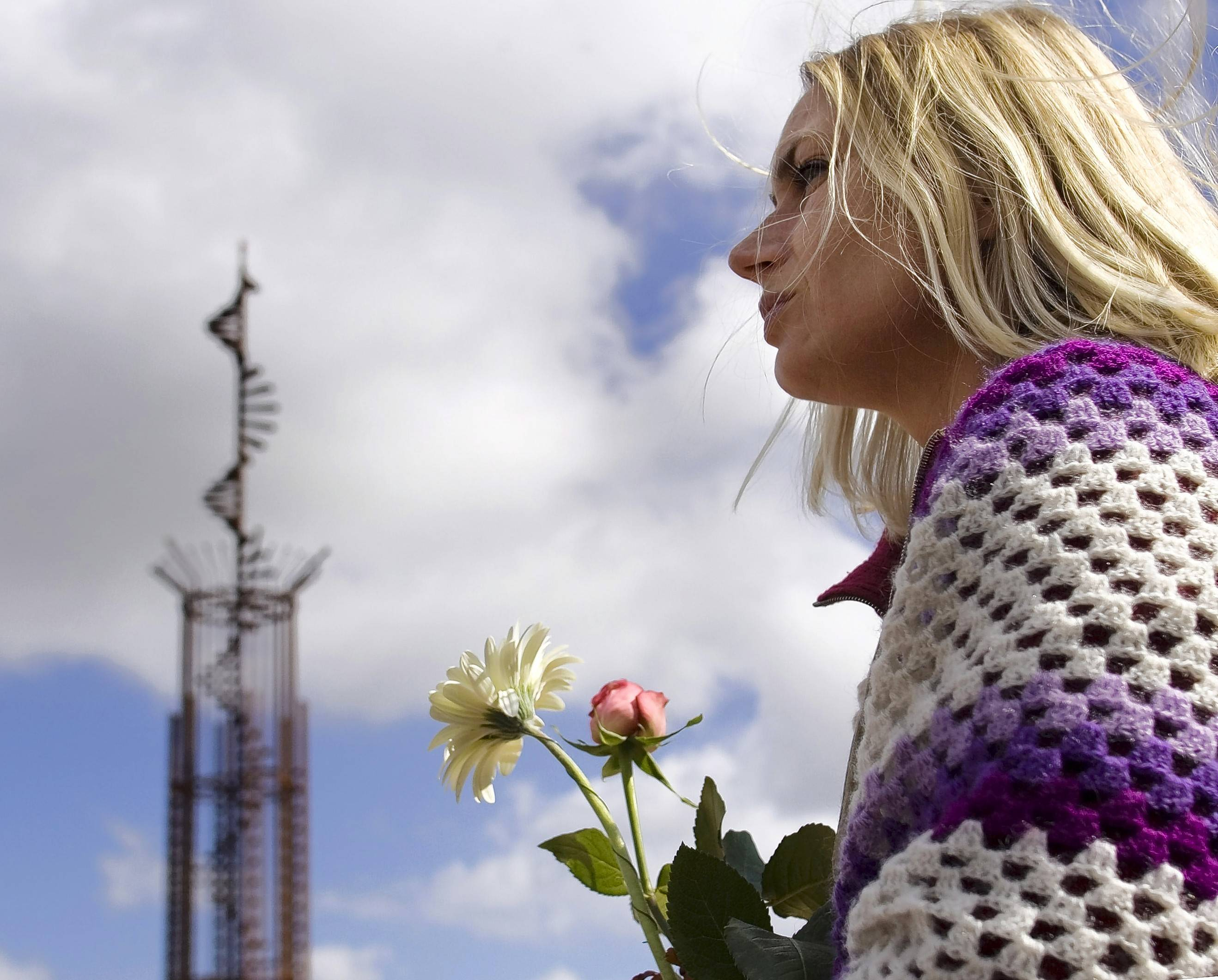 "A woman holds a flower tribute near the ""Winding Stairs"" monument dedicated to those who lost their lives when a KLM jet crashed into a Pan Am 747 as it attempted to take off at Los Rodeos Airport in Santa Cruz de Tenerife, Canary Islands."