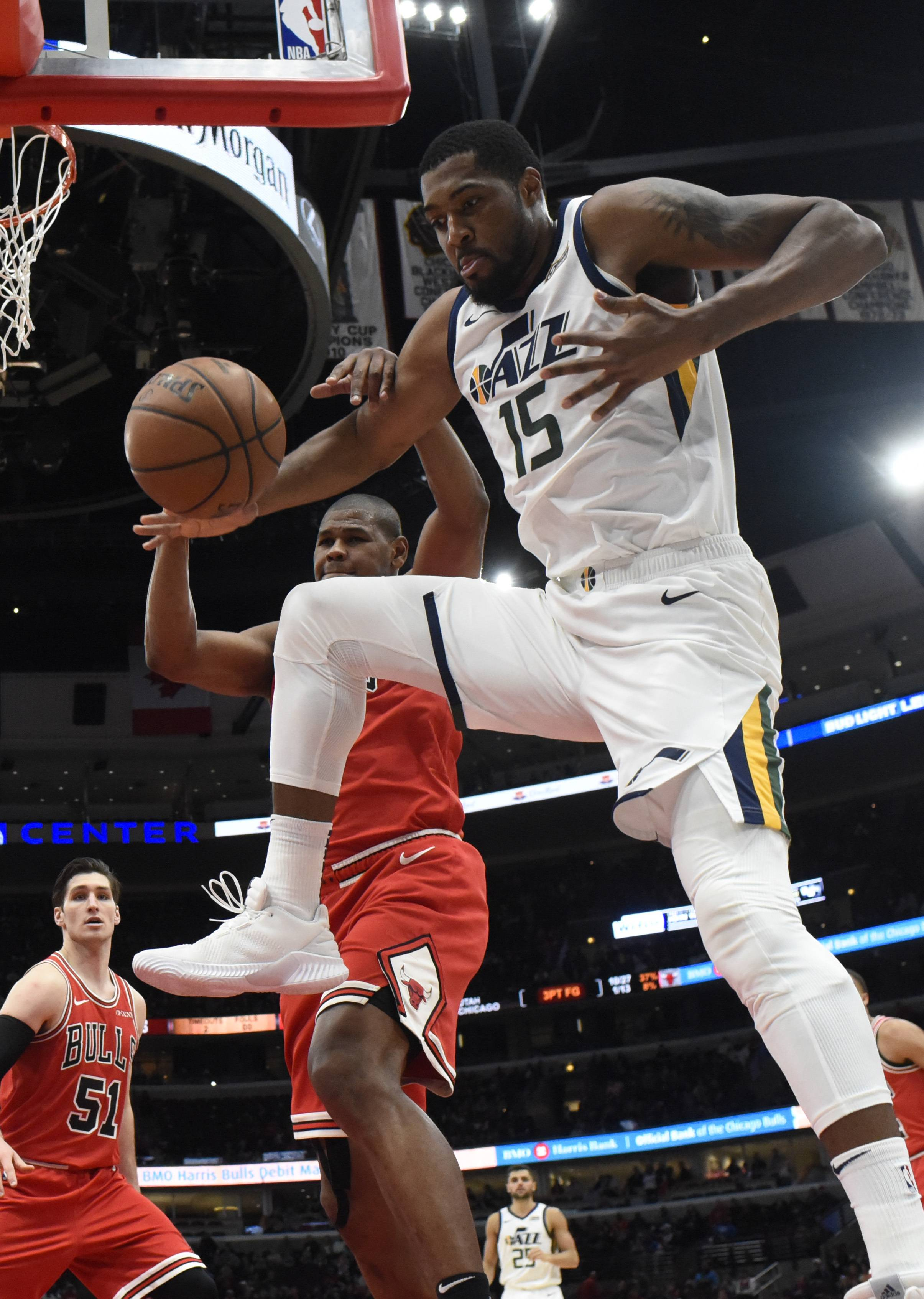 Utah Jazz forward Derrick Favors (15) and Chicago Bulls forward Cristiano Felicio (6) go for a lose ball during the second half of an NBA basketball game Saturday, March 23, 2019, in Chicago. The Jazz won 114-83. (AP Photo/David Banks)