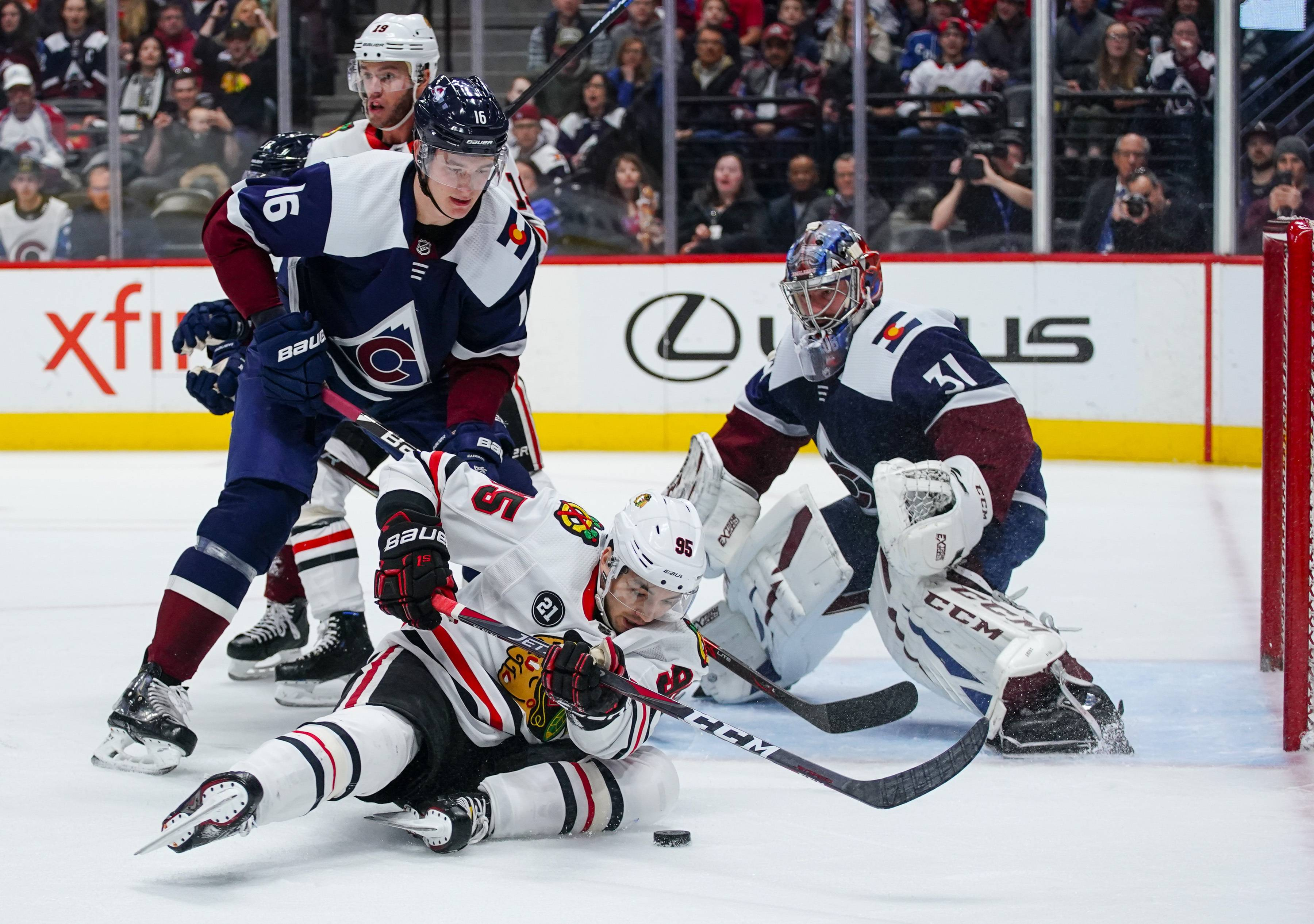 Chicago Blackhawks right wing Dylan Sikura (95) slides on the ice to control the puck against Colorado Avalanche defenseman Nikita Zadorov (16) and Philipp Grubauer (31) during the first period Saturday in Denver.