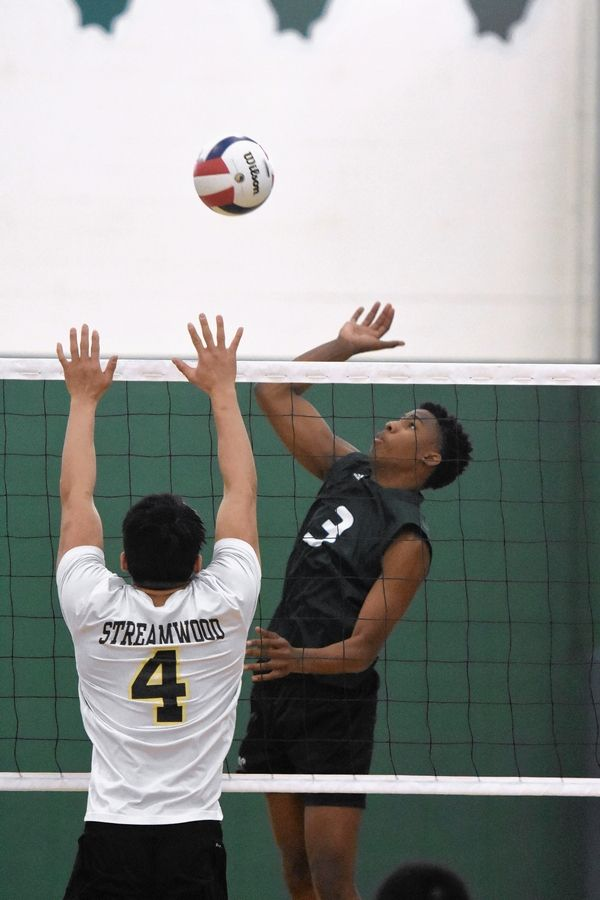 Grayslake Central's Emmanuel Eugene (3) hits against Streamwood's Bryan Aguada Saturday during the Grayslake Central boys volleyball tournament.