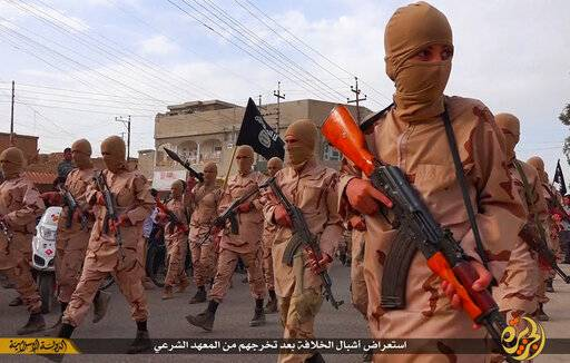 "FILE - In this file photo released on April 25, 2015, by a militant website, which has been verified and is consistent with other AP reporting, young boys known as the ""caliphate cubs"" hold their rifles as they parade after graduating from a religious school, in Tal Afar, near Mosul city, north Iraq. The Arabic words, center, read: ""A parade of caliphate cubs after their graduation from a religious school."" (Militant website via AP, File)"