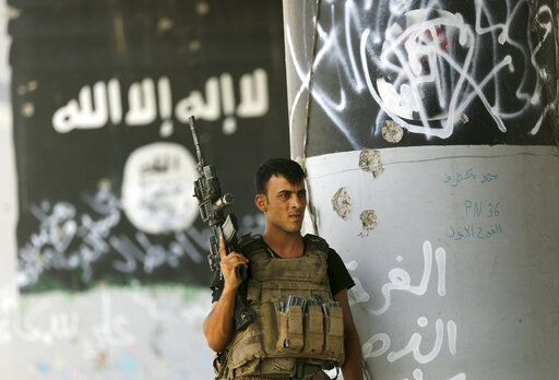 FILE - In this June 27, 2016, file photo, a member of Iraqi counterterrorism forces stands guard near Islamic State group militant graffiti in Fallujah, Iraq.