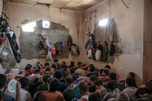 FILE -In this Tuesday, July 18, 2017, file photo, suspected Islamic State members sit inside a small room in a prison south of Mosul.