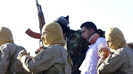 FILE - This Wednesday, Dec. 24, 2014, this image posted by the Raqqa Media Center, which monitors events in territory controlled by Islamic State militants with the permission of the extremist group, shows militants with a captured pilot, center right, wearing a white shirt in Raqqa, Syria.