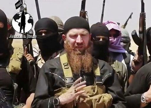 FILE - This file image made from undated video posted during the weekend of June 28, 2014, on a social media account frequently used for communications by the Islamic State of Iraq and the Levant (ISIL), which has been verified and is consistent with other AP reporting, shows Omar al-Shishani standing next to the group's spokesman among a group of fighters as they declare the elimination of the border between Iraq and Syria.