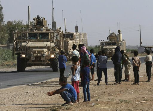 FILE - In this July 26, 2017, file photo, Syrians look at a U.S. armored vehicle convoy on a road that leads to Raqqa, northeast Syria.