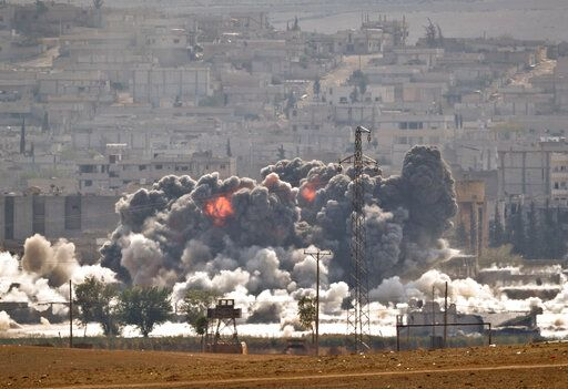FILE - In this October 28, 2014, file photo, smoke and flames rise from an Islamic State fighters' position in the town of Kobani during airstrikes by the US-led coalition seen from the outskirts of Suruc, near the Turkey-Syria border.