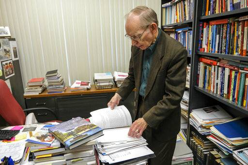 "John Jackson, a professor at SIU for 50 years, leafs through the various manuscripts from contributors that he edited and compiled into ""Southern Illinois University at 150 Years,"" a book commemorating the university's 150th anniversary this year on March 5, 2019.  (Byron Hetzler /The Southern Illinoisan via AP)"