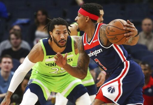 Washington Wizards' Bradley Beal, right, drives against Minnesota Timberwolves' Derrick Rose in the first half of an NBA basketball game Saturday, March 9, 2019, in Minneapolis.