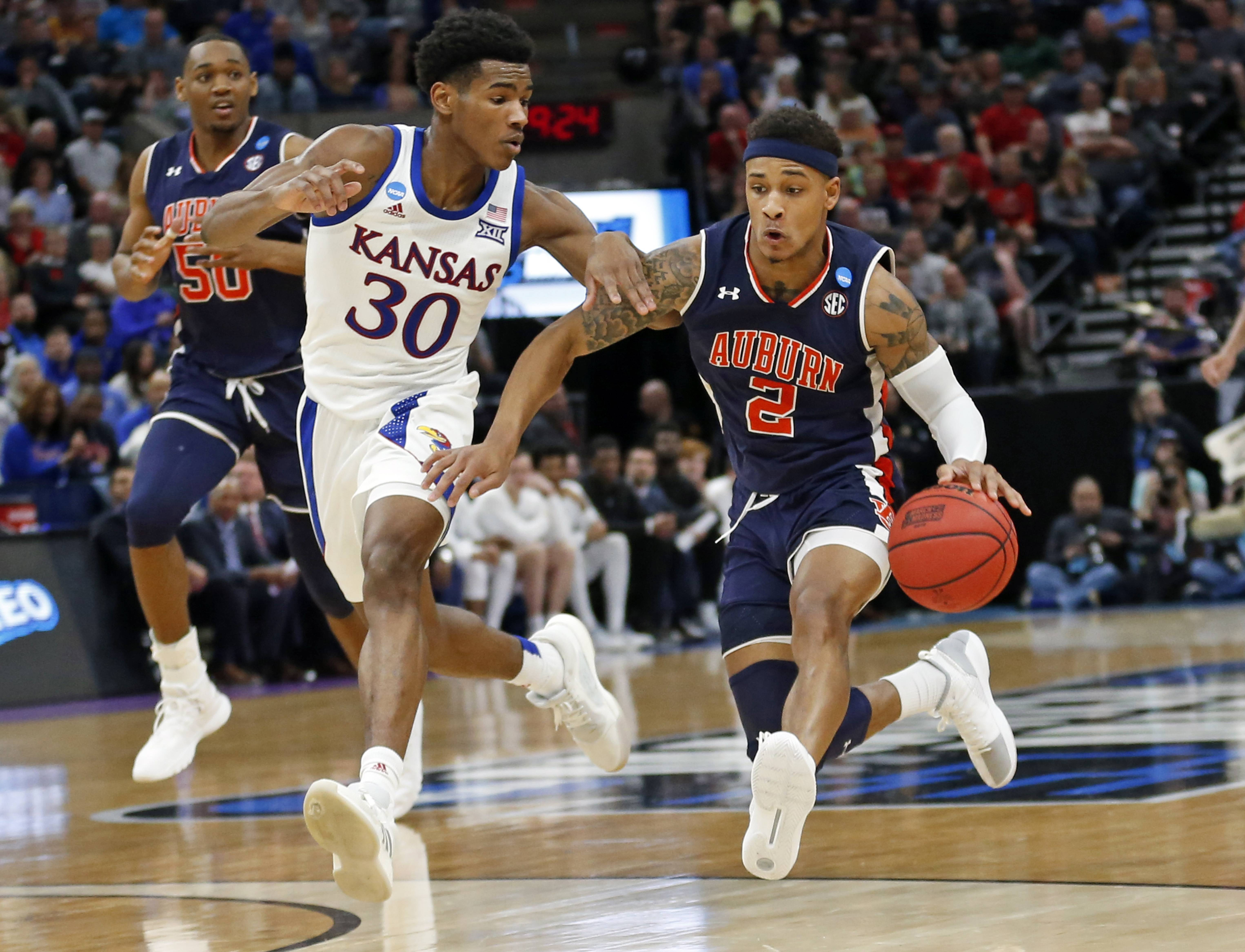 Auburn guard Bryce Brown (2) brings the ball up court as Kansas guard Ochai Agbaji (30) defends Saturday during the second half of a NCAA Tournament game in Salt Lake City.