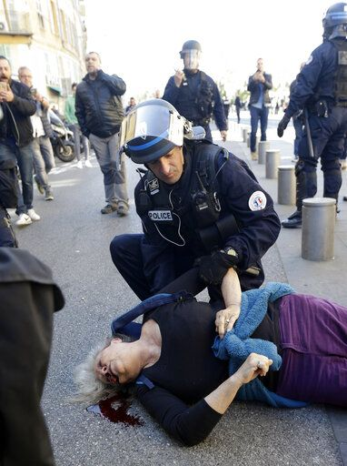 "EDS NOTE: GRAPHIC CONTENT. FILE - In this Saturday, March 23, 2019 file picture, a police officer looks at anti-globalization activist Genevieve Legay, 73, as she lies unconscious after collapsing on the ground during a protest in Nice, southeastern France, as part of the 19th round of the yellow vests movement. Genevieve Legay was waving a rainbow flag marked ""Peace"" and a yellow vest when riot police carrying shields suddenly pushed toward the group of a few dozen protesters Saturday."
