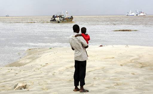 A man holding his child watches a boat carrying displaced familie arrive after being rescued from a flooded area of Buzi district, 200km outside Beira, Mozambique, Saturday, March 23, 2019. A second week has begun with efforts to find and help some tens of thousands of people in devastated parts of southern Africa, with some hundreds dead and an unknown number of people still missing.