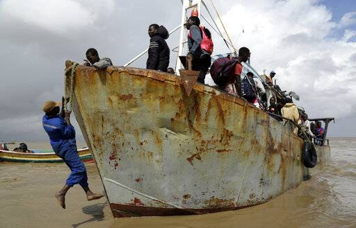 A man docks a boat carrying displaced families after being rescued from a flooded area of Buzi district, 200km outside Beira, Mozambique, Saturday, March 23, 2019. A second week has begun with efforts to find and help some tens of thousands of people in devastated parts of southern Africa, with some hundreds dead and an unknown number of people still missing.
