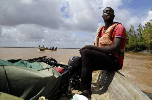 A fisherman navigates a wooden boat to Buzi district, 200 kilometers (120 miles) outside Beira, Mozambique, Saturday, March 23, 2019. A second week has begun with efforts to find and help some tens of thousands of people in devastated parts of southern Africa, with some hundreds dead and an unknown number of people still missing.
