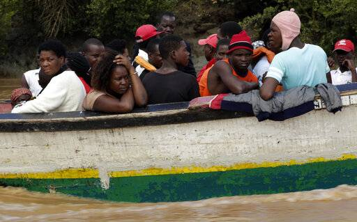 Passengers of a wooden boat travel to Buzi district, 200 kilometers (120 miles) outside Beira, Mozambique, on Saturday, March 23, 2019. A second week has begun with efforts to find and help some tens of thousands of people in devastated parts of southern Africa, with some hundreds dead and an unknown number of people still missing.