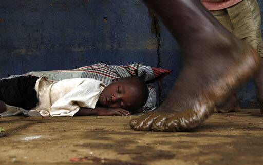 A displaced young boy sleeps on the floor at a school in Buzi district, 200 kilometers (120 miles) outside Beira, Mozambique, on Saturday, March 23, 2019. People left the cyclone-shattered city of Beira for the town of Buzi, which for a week people had been fleeing to with little but their clothes.