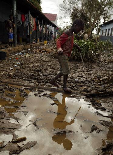 A young boy walks through a muddy walkway in Buzi district, 200 kilometers (120 miles) outside Beira, Mozambique, on Saturday, March 23, 2019. A second week has begun with efforts to find and help some tens of thousands of people in devastated parts of southern Africa, with some hundreds dead and an unknown number of people still missing.